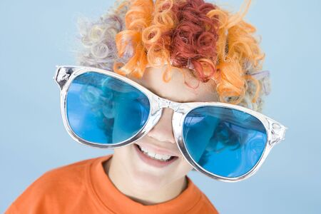 dressing up costume: Young boy wearing clown wig and sunglasses smiling
