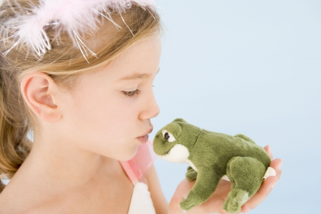 dressing up costume: Young girl in princess costume kissing plush frog