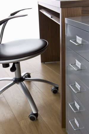 desk tidy: Empty Chair And Desk With Filing Cabinet
