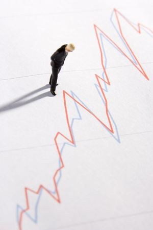 likeness: Figurine Of A Businessman Standing On A Line Graph