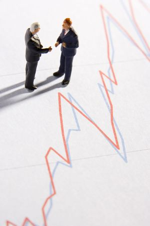 Figurines Of Two Businessmen Shaking Hands On A Line Graph photo