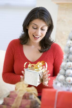 opening gift: Woman Excited To Open Christmas Present