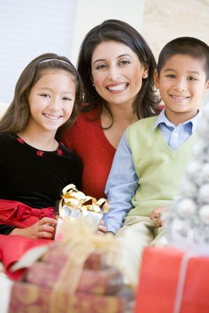 Mother With Her Son And Daughter Holding Christmas Gifts photo