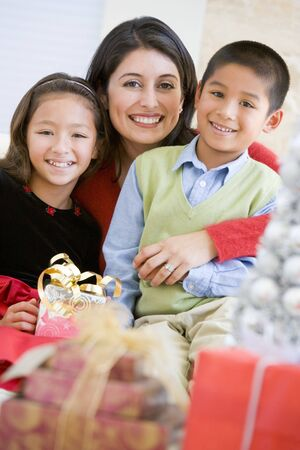 Mother With Her Daughter And Son Holding Christmas Gifts photo