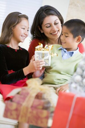 Mother Sitting With Her Son And Daughter,Exchanging Christmas Gifts photo
