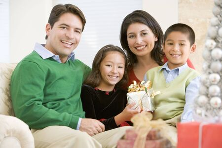 latinos: Family Sitting On Sofa Together,Holding A Christmas Gift