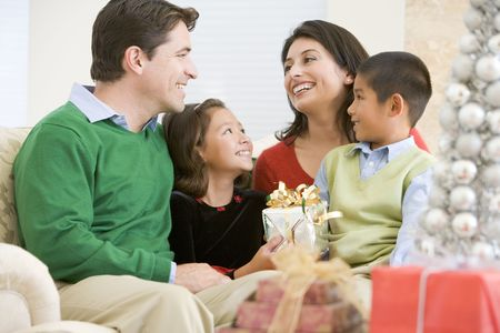 family living: Family Smiling At Each Other,Holding Christmas Gift
