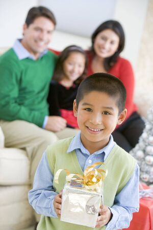 adult christmas: Young Boy Standing Holding Christmas Present,With His Parents And Sister In The Background