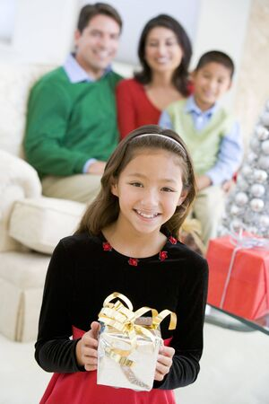 Young Girl Standing Holding Christmas Present,With Her Parents And Brother Sitting In The Background photo