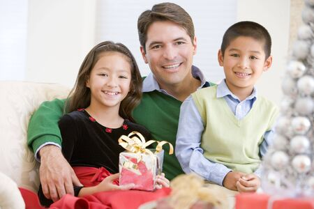 Father And His Son And Daughter Sitting On Sofa,Holding A Christmas Present photo