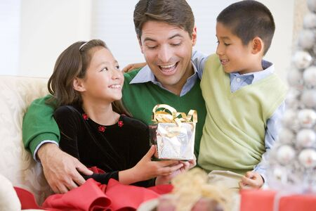 three presents: Father Being Given A Christmas Present By His Daughter And Son