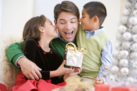 pere noel: P�re Etant donn� un cadeau de No�l par sa fille et son fils Banque d'images