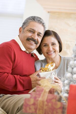 latino: Middle Aged Couple Sitting On Sofa Holding Christmas Present