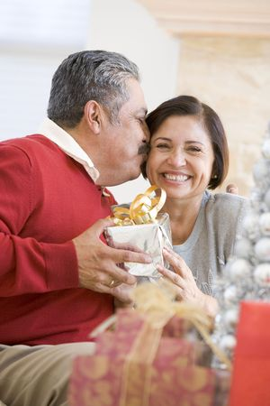 Middle Aged Couple Affectionately Sitting And Holding Christmas Present Stock Photo - 3724925