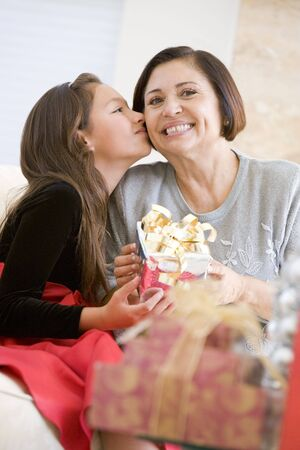 Granddaughter Kissing Grandmother On The Cheek,And Giving Her A Christmas Gift photo