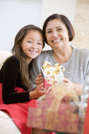 Grandmother And Granddaughter Sitting On Sofa Holding A Christmas Gift photo