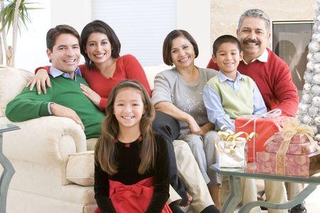 ni�os latinos: Familia, todos sentados alrededor de una mesa de caf� y regalos de Navidad Foto de archivo