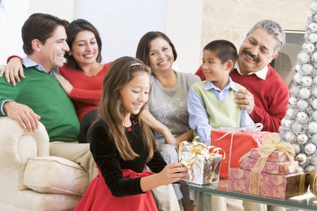 Family Sitting On Sofa In Front Of Christmas Presents,Young Girl Selecting A Gift photo