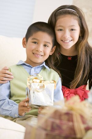 Brother And Sister Sitting On Couch Holding Christmas Gift Stock Photo - 3724837