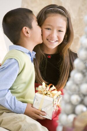 Brother Kissing His Sister On The Cheek,And Holding A Christmas Gift photo