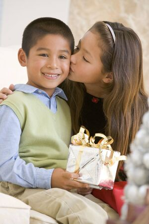 elementary age girls: Sister Giving Her Brother A Christmas Present And Kissing Him On The Cheek