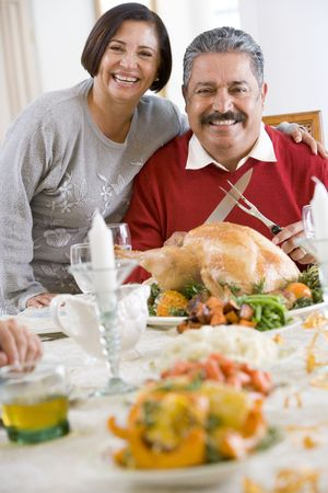 Woman With Her Arm Around Her Husband,Who Is Getting Ready To Carve A Turkey photo