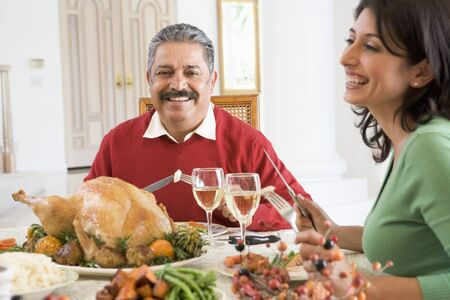 Father And His Adult Daughter Sitting Down For Christmas Dinner photo