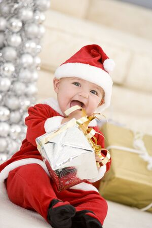 dressing up costume: Baby In Santa Costume At Christmas Stock Photo