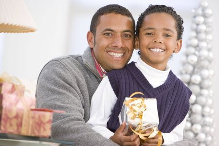 9 year old: Father And Son Hugging,Holding Christmas Gift