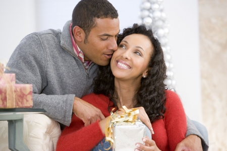 Husband And Wife Affectionately Exchanging Christmas Gifts Stock Photo - 3724861