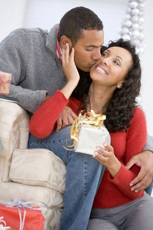 couple home: Husband And Wife Affectionately Exchanging Christmas Gifts Stock Photo