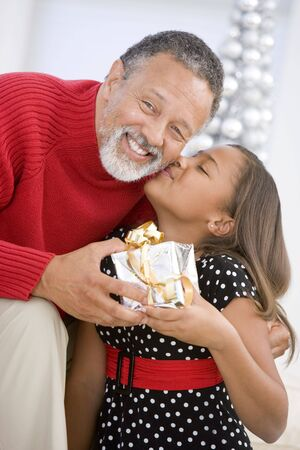 grandkids: Grandfather Giving His Granddaughter A Christmas Present Stock Photo