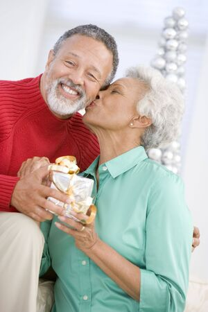 Senior Couple Exchanging A Christmas Gift Stock Photo - 3724804