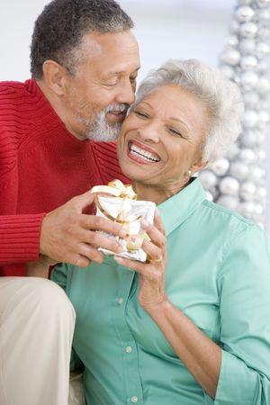 Senior Couple Exchanging A Christmas Gift Stock Photo - 3724842