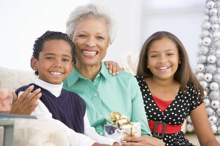 Grandmother Sitting With Her Two Grandchildren,Holding A Christmas Gift photo
