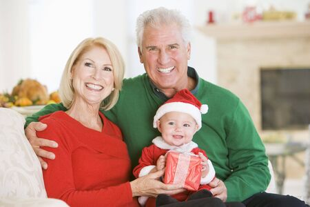 Grandparents With Baby In Santa Outfit photo
