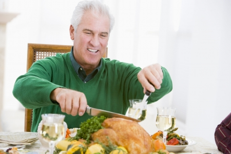Man Carving Up Turkey At Christmas Dinner photo