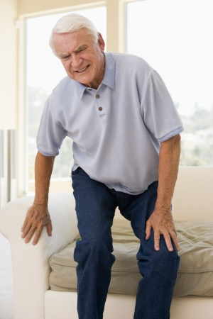 senior pain: Senior Man Trying To Sit Down Stock Photo