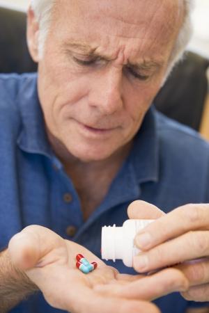 elderly pain: Senior Man Out Pouring Pillole di bottiglia