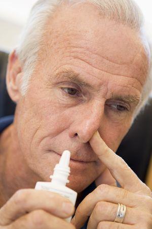 wincing: Senior Man Using Nasal Spray