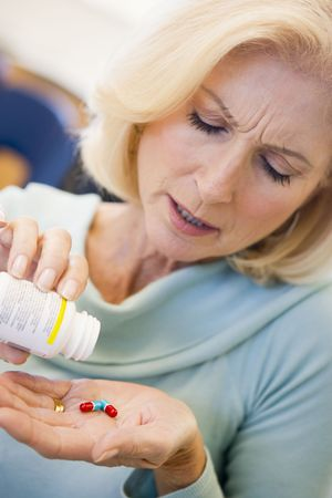 Senior Woman Pouring Pills Out Of Bottle photo