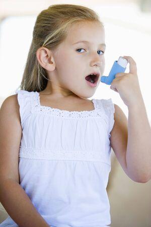 asma: Chica usando un inhalador