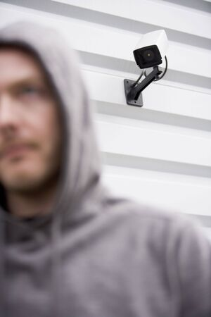 Surveillance Camera And Young Man In Hooded Sweatshirt photo
