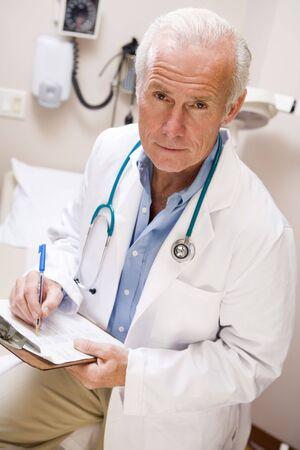 Middle Aged Doctor Writing On His Clipboard Stock Photo - 3723703