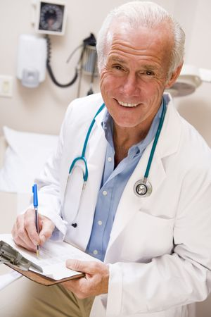 Middle Aged Doctor Writing On His Clipboard Stock Photo - 3723708