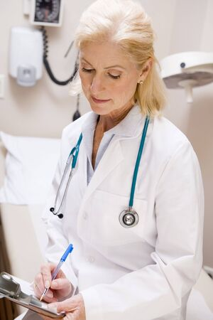 Middle Aged Female Doctor Writing On A Clipboard Stock Photo - 3723707
