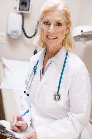 fmale: Middle Aged Female Doctor Writing On A Clipboard