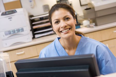 A Nurse Sitting At A Computer At The Reception Area Of A Hospital Stock Photo - 3724190
