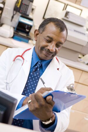 A Doctor Writing On A Clipboard At The Reception Area Of A Hospital Stock Photo - 3724389