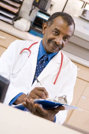 A Doctor Writing On A Clipboard At The Reception Area Of A Hospital Stock Photo - 3724146
